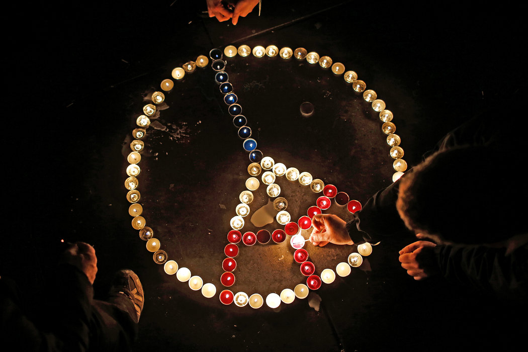 People lighting candles at the Place de la République in Paris. Credit Laurent Cipriani/Associated Press