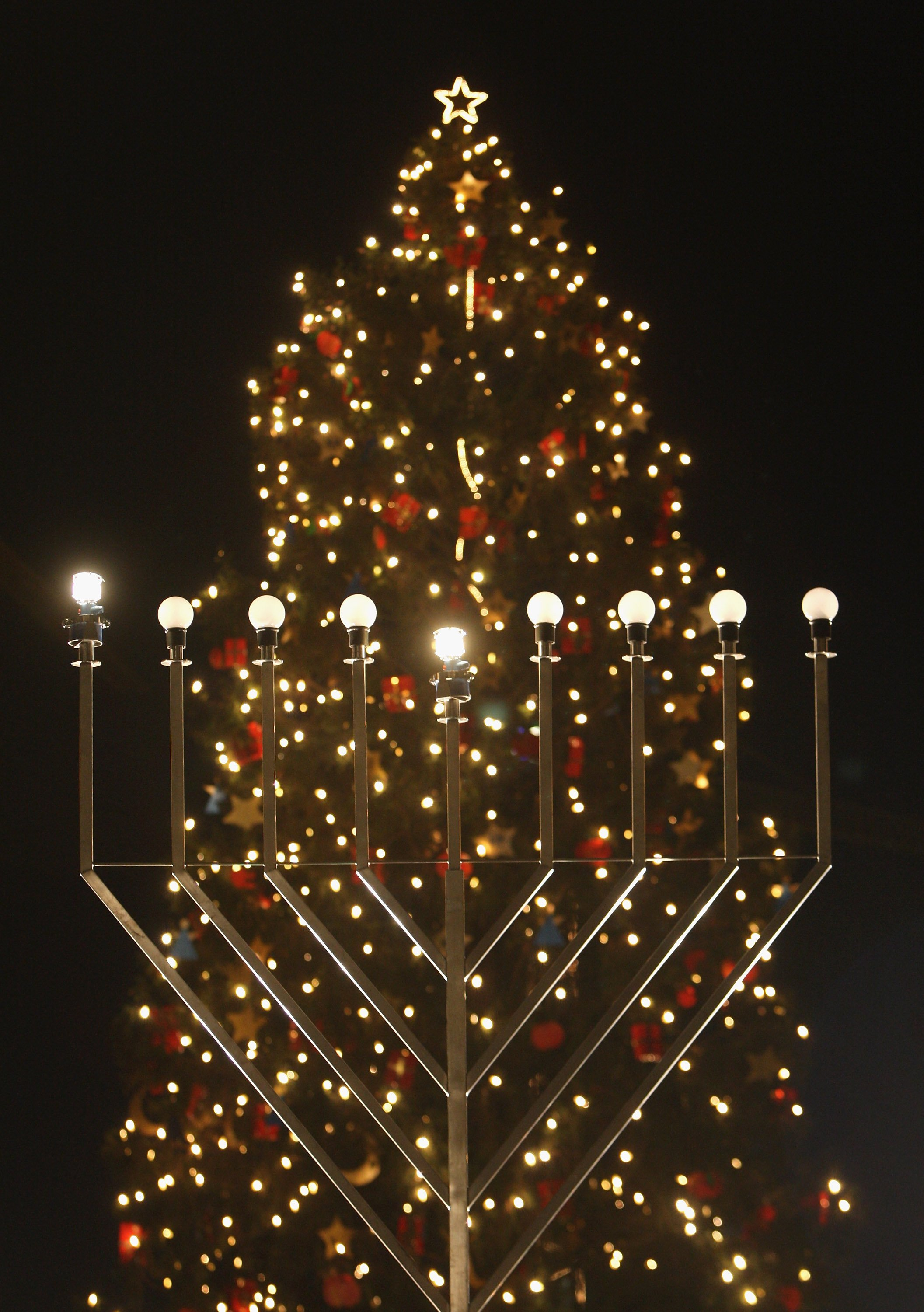 Sean Gallup—Getty Images A giant, gas-lit menorah stands in front of a Christmas tree shortly after members of the local Jewish community lit the menorah on the night before the first day of Hannukah on Dec. 4, 2007 in Berlin, Germany.