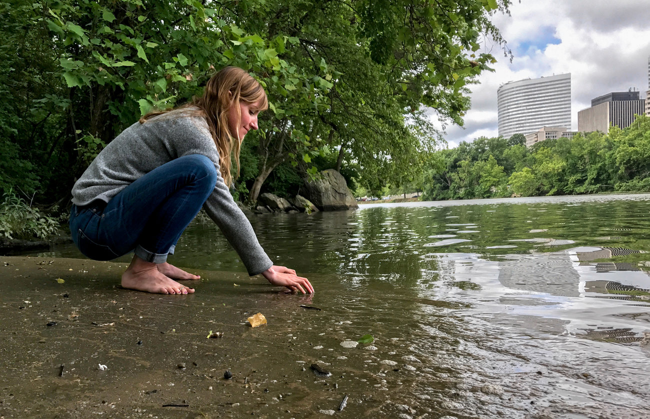 """Clare Kelley practices """"forest bathing"""" along the edge of an urban forest on Roosevelt Island, in the middle of the Potomac River. In contrast to hiking, forest bathing is less directed, melding mindfulness and nature immersion to improve health. Allison Aubrey/NPR"""