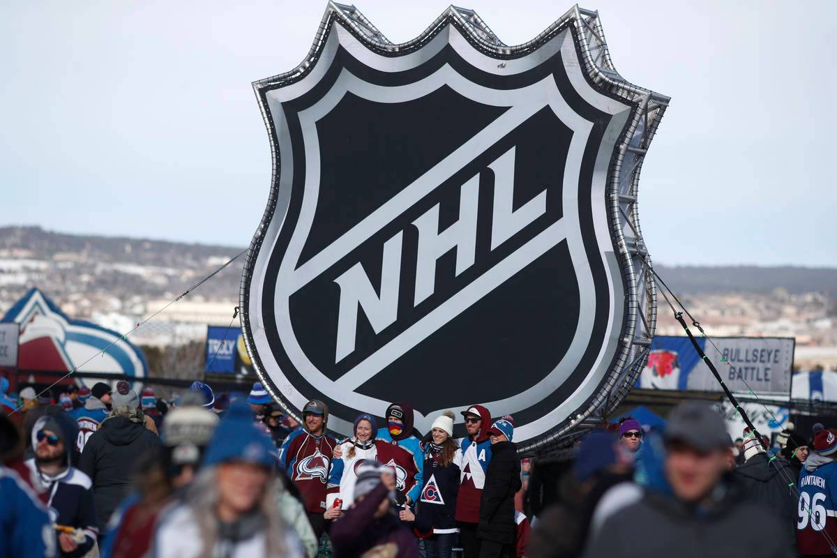 FILE - In this Feb. 15, 2020, file photo, fans pose below the NHL league logo at a display outside Falcon Stadium before an NHL Stadium Series outdoor hockey game between the Los Angeles Kings and Colorado Avalanche, at Air Force Academy, Colo. (AP Photo/David Zalubowski, File)